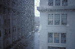 view of loft buildings through rainy window