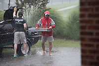 NWA Democrat-Gazette/J.T. WAMPLER Loren Shackelford of Fayetteville wades barefoot through rain water Wednesday Aug. 5, 2015 to bring burgers and hot dogs to hungry high school golfers playing in the Springdale Bulldog Invitational at the Springdale Country Club. A line of severe weather forced a delay in the tournament causing golfers and spectators to scramble for cover. Micah Thompson of Springdale, left, closed up the grill but the rain extinguished the coals as the golf course received an inch of water in under an hour.