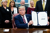 US President Donald J. Trump (C) holds up 'H.R. 724, the Preventing Animal Cruelty and Torture Act', after signing it during a ceremony in the Oval Office of the White House in Washington, DC, USA, 25 November 2019.<br /> Credit: Michael Reynolds / Pool via CNP/AdMedia