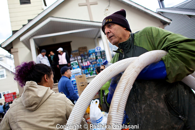 MIDLAND BEACH, NEW YORK-NOVEMBER 3:  A man carries equipment from the Oasis Christian Center to help pump water out of a basement in the aftermath of Hurricane Sandy November 3, 2012 in Midland Beach in the Staten Island borough of New York City. Staten Island saw an influx of volunteers today as it tries to recover from the devastating storm that left 19 dead on the island.