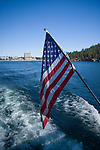 Idaho,North,Coeur d'Alene. An American flag flys from the stern of a tour boat with the waterfront town of Coeur d'Alene distant.