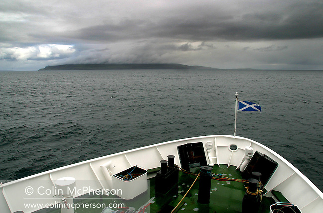 A Saltire fluttering at the bow of the Caledonian MacBrayne ferry Loch Nevis as it approaches the Hebridean island of Eigg on its daily run from Mallaig on the Scottish mainland. The island of Eigg was one of a chain of islands which lie of Scotland's west coast and was accessible by a state-run lifeline service from the mainland. The residents on Eigg organised a buy-out of the island in the late 1990s and took it into community ownership...
