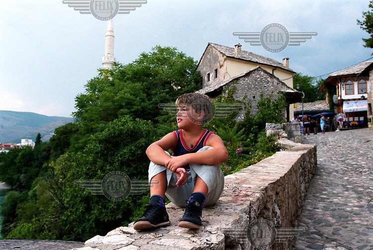 A boy sitting on the edge of the Neretva river. During the Bosnian war, the medieval town of Mostar was split along the river, with the Muslim community on one side and Bosnian Croats on the other. Severely damaged in the fierce fighting, the town is now being restored to its former beauty.