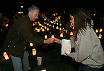 "SOUTHBURY, CT 01/01/08-010108BZ01- Ken Aspis, of Southbury, hands a lit candle to Lisamarie Farina, 19, of Southbury, while setting up luminaries to form the word ""HOPE"" on the lawn outside Sacred Heart Church in Southbury Tuesday night.   The vigil was in remembrance of youth from the area who had untimely deaths recently.<br /> Jamison C. Bazinet Republican-American"