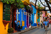 Tourists walk along the colorfully painted colonial houses in the street located within the historical walled city in Cartagena, Colombia, 12 December 2017. With the peace agreement, ending a 52-year civil conflict and promising political stability, together with rapid economic growth and unexploited tourism potential, Colombia has truly become a holiday destination. Cartagena, a UNESCO World Heritage site on the tropical Caribbean coast, plays the primary role in Colombia's tourism renaissance. The historic sites from the Spanish colonial times are being restored, private investments are visible throughout the city and an increased number of local people benefit from the boom of the travel related services.