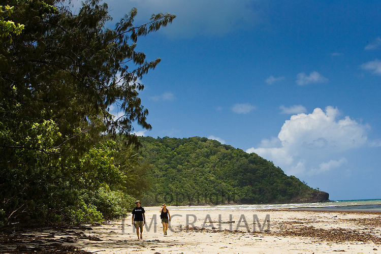 Couple walk on Myall Beach by Cape Tribulation, named by Captain Cook, Queensland, Australia