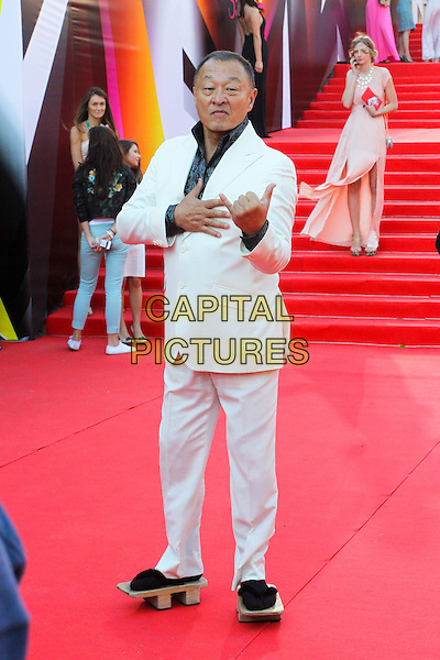 Cary-Hiroyuki Tagawa<br /> The opening of the Moscow International Film Festival, Moscow, Russia.<br /> June 20th, 2013<br /> full length white suit jacket black shirt hand sign devil fingers gesture arms shoes wood wooden platform sandals asian japanese geta socks<br /> CAP/PER/LS<br /> &copy;LS/PersonaStars/CapitalPictures