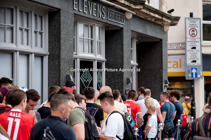 """Pictured: Queues of people outside Elevens Bar in Cardiff, Wales, UK. Thursday 12 July 2018<br /> Re: Last night (Thurday 12 July) Elevens Bar & Grill and the Football Association of Wales jointly hosted a Q&A evening with Gareth Bale. At the event, Gareth unveiled a new piece of memorabilia for Elevens – his match worn boots from this year's Champions League Final with which he scored that incredible overhead kick.<br /> The event, hosted at Elevens Bar & Grill was open to members of the public with doors opening at 6pm on Thursday evening. People started queueing from 3pm, with a cross-section of fans of all ages in Wales shirts and bucket hats. <br /> The Q&A, conducted by Ian Gwyn Hughes from the FAW, discussed all aspects of his career so far, from growing up in Cardiff to winning 4 Champions League medals with Real Madrid. On growing up in Whitchurch, Gareth said: """"My family were a huge influence on me growing up. My parents were so supportive, taking me here there and everywhere so I could play football. Growing up I can hardly remember not being with a football – I even took one to bed!""""<br /> There were a lot of youngsters in the audience, eager to hear from their hero. Gareth's advice to them? """"Work hard for what you want and who knows where that could take you.""""<br /> As a left-footer, Ryan Giggs,  Wales' national team manager was someone he looked up to growing up. Gareth mentioned it was great to beat Ian Rush's goal scoring record for Wales with his childhood idol as manager. """"I knew I'd levelled his record at half time, I needed one more to break it. The manager wanted to take me off but I said give me another 15 minutes to see if I can do it. Luckily on 61 minutes our goalkeeping coach took too long to do the substitution on the paper, so it gave me an extra minute. It worked out perfectly."""""""