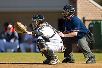 Catcher Daniel Gerow #15 of the Davidson Wildcats sets a target as home plate umpire Brian Kennedy looks on during the game against the College of Charleston Cougars at Wilson Field on March 12, 2011 in Davidson, North Carolina.  The Wildcats defeated the Cougars 8-3.  Photo by Brian Westerholt / Four Seam Images