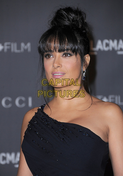 Salma Hayek.at The LACMA 2012 Art and Film Gala held at LACMA in Los Angeles, California, USA, October 27th 2012..portrait headshot fringe bun hair up  beaded black  navy blue one shoulder .CAP/RKE/DVS.©DVS/RockinExposures/Capital Pictures.