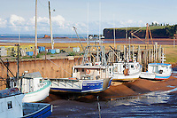 Fishing boats are beached in the small harbour as the tide goes out in Fundy Bay