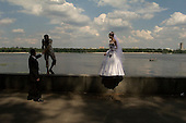 Kiev, Ukraine<br /> July 23, 2005 <br /> <br /> Wedding parties arrive by the dozens at the monument  to: Kyj, Shchek, Khoriyv and their sister Libyd, the legendary founders of Kiev to have their photo taken on a Saturday afternoon. It is a weekend tradition.