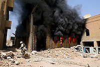 Baghdad, Iraq, May 20, 2003.A US soldier walks by one of the buildings inside the Iraqi TV complex, set on fire this morning by unidentified looters.