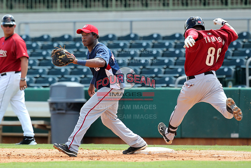 Washington Nationals first baseman Estarlin Martinez #7 waits for the ball as Jose Carlos Thompson #86 beats the throw during an Instructional League game against the Houston Astros at Osceola County Stadium on September 26, 2011 in Kissimmee, Florida.  (Mike Janes/Four Seam Images)