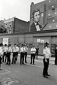 1981: police stand guard on the corner of Westbourne Park Road and Portobello Road beneath a wall painting of Abraham Lincoln during the Notting Hill Carnival