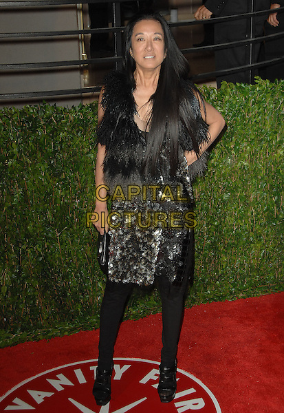 VERA WANG.The 2010 Vanity Fair Oscar Party held at The Sunset Tower Hotel in West Hollywood, California, USA..March 7th, 2010.oscars full length paillettes silver black brown beige wrap dress tights hand on hip fur.CAP/RKE/DVS.©DVS/RockinExposures/Capital Pictures.