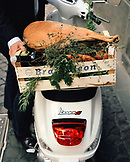 ITALY, Orvieto, Umbira, person standing with basket of vegetables and prosciutto on a Vespa.