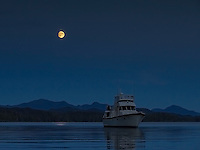 The motor yacht Great Bear II sits at anchor as the moon rises over coastal British Columbia.