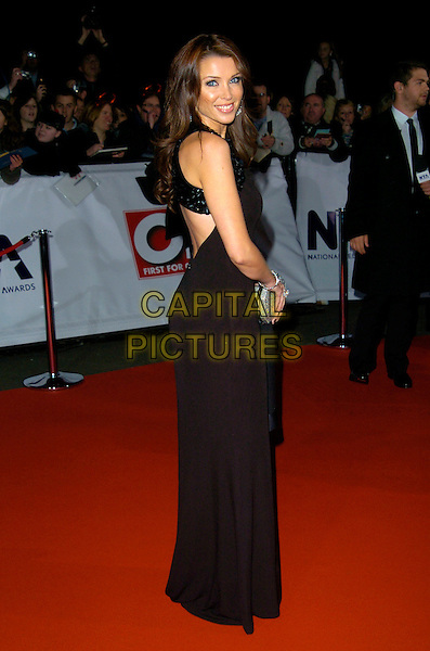 DANNII MINOGUE.The National Television Awards, Royal Albert Hall, London, England..October 31st, 2007.TV NTA full length black dress sleeveless silver clutch purse cut out away looking over shoulder .CAP/CAN.© Can Nguyen/Capital Pictures