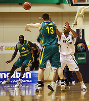 Boomers centre Aron Baynes passes to forward Nathan Jawai under pressure from Mike Vukona (right).<br />