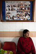 A pregnant woman waits for the doctors' appointment under the board of photographs of previous western clients at the Akanksha Infertility and IVF Clinic in Anand, Gujarat, India. The centre has become the most popular clinic for outsourcing pregnancies by western couples.
