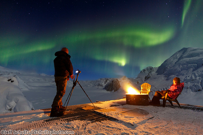 Women take photos and view the Aurora from the deck and around a camp fire at the Sheldon Chalet in the Alaska Range. Ruth Glacier and Amphitheater.  Winter