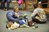NWA Democrat-Gazette/Michael Woods --01/14/2015-- w @NWAMICHAELW... Calie Becker, age 7, reads a book to Erin Renollet Children's Assistant with the Springdale Public Library and Banjo, a therapy dog, during Wednesday evenings session of the Kibbles and Books program at the Springdale Public Library. Kibbles & Books is a literacy program designed to build confidence in young readers by reading out loud to therapy dogs giving the children a chance to practice their literacy skills in a stress-free and fun context.