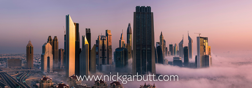 Downtown Dubai skyline at dawn, with unusual low cloud and mist rolling in. Dubai, United Arab Emirates. April 2013
