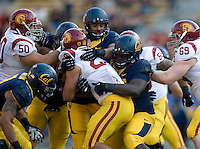 Antione Davis of California and his teammates tackle USC running back during NCAA football game at Memorial Stadium in Berkeley, California on November 9th, 2013.   USC defeated California, 62-28.
