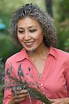 Asian woman in her garden with sprig of lavandar