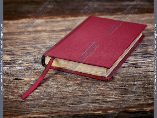 Small red hardcover book on wooden table background