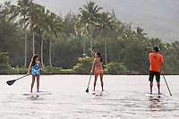 Mother and daughter converse during a family standup paddling lesson on the Wailua River, Kaua'i.