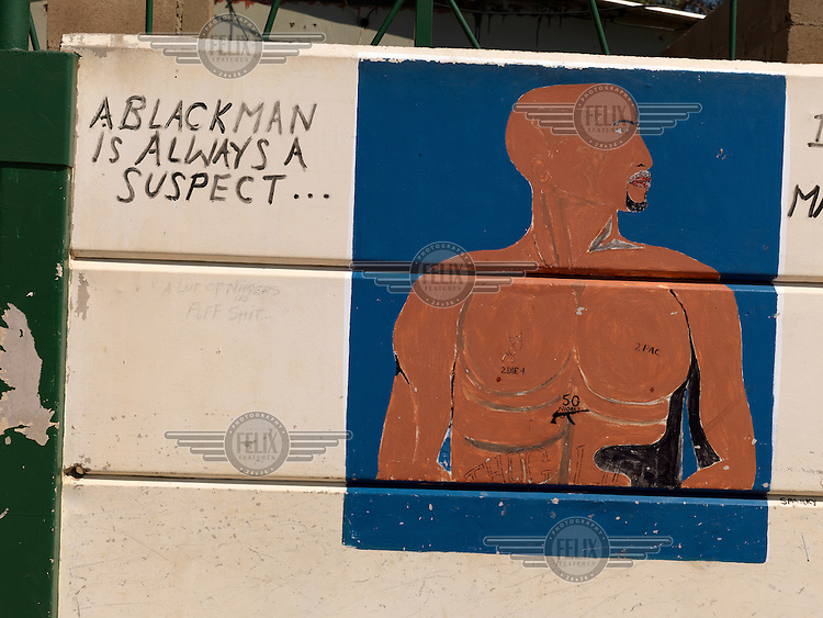 A Tupac Shakur mural painted on the outside of a tavern, next to a grafitti that reads 'A BLACKMAN IS ALWAYS SUSPECT...'..
