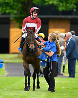 Winner of The ROA/Racing Post Owners' Jackpot Handicap (Class 5) Desert Cross ridden by Fran Berry and trained by Jonjo O'Neill  is led into the winners enclosure during Afternoon Racing at Salisbury Racecourse on 12th June 2018