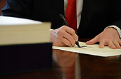 United States President Donald J. Trump signs the $1.5 trillion tax cut bill, stacked on his desk, in the Oval Office of the White House, December 22, 2017, in Washington, DC, prior to his departure to Mar-a-Lago, Florida for the holidays. <br /> Credit: Mike Theiler / Pool via CNP