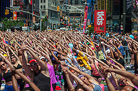 """Thousands of yoga practitioners pack Times Square in New York to participate in a mid-day Bikram Yoga class on the first day of summer, Friday, June 21, 2013. The 11th annual Solstice in Times Square, """"Mind Over Madness"""",  stretches the yogis' ability to block out the noise and the visual clutter that surround them in the Crossroads of the World"""". (© Richard B. Levine)"""