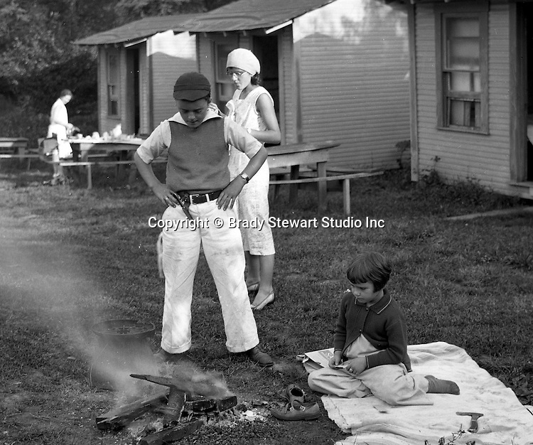 Markleysburg PA:  Stewart family camping out at the Lone Star Inn's cabins near Youghiogheny Lake - 1931.  Brady Jr., and Sally Stewart putting out a campfire in front of rental cabin, family having lunch before going to Youghiogheny Lake 1931
