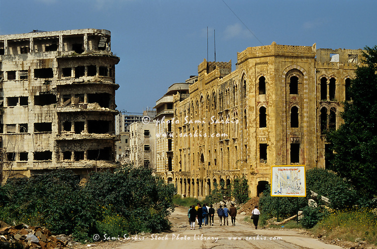 People walking past buildings destroyed by the Lebanese Civil War, Beirut, Lebanon.