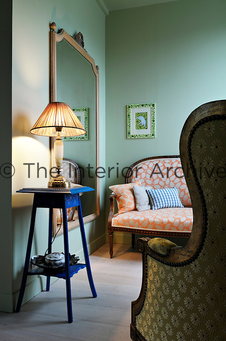 A small sofa faces an armchair in a corner of the bedroom, both newly reupholstered in a complementary pattern
