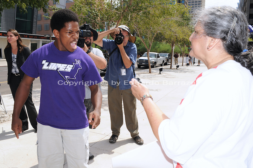 Phoenix, Arizona. July 24, 2012 - Jarvis Johnson (left) and Martha Payan (right) hold a heated verbal argument over Sheriff Arpaio outside the Sandra Day O'Connor United States Federal Courthouse in Phoenix, Arizona as Arpaio testifies in court. Maricopa County Sheriff Joe Arpaio testified in court on July 24, 2012 to respond to accusations his office (MCSO) has been racial profiling Latinos as they enforce local immigration laws in the county. The lawsuit is known as Ortega-Melendres vs. Arpaio. Photo by Eduardo Barraza © 2012