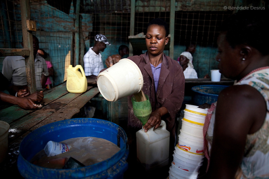Alice(C) and Mary(R) working at the Madiaba Busaa Club in a Nairobi slum on april 7, 2013. Both have been selling Busaa, a traditional fermented beer, for many years. Busaa is made by crudely fermenting maize, millet, sorghum or molasses. At Kshs 35 per liter it is much cheaper than a Kshs120 half-liter bottle of commercial beer. The local brew was legalised in 2010 and since then busaa clubs have become increasingly popular. Drinking is on the rise in Kenya, especially among young people. Photo by Benedicte Desrus