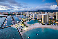 An aerial view at sunset of Ala Wai Harbor, the Hilton Hawaiian Village's lagoon and Kahanamoku Beach, Waikiki, O'ahu.