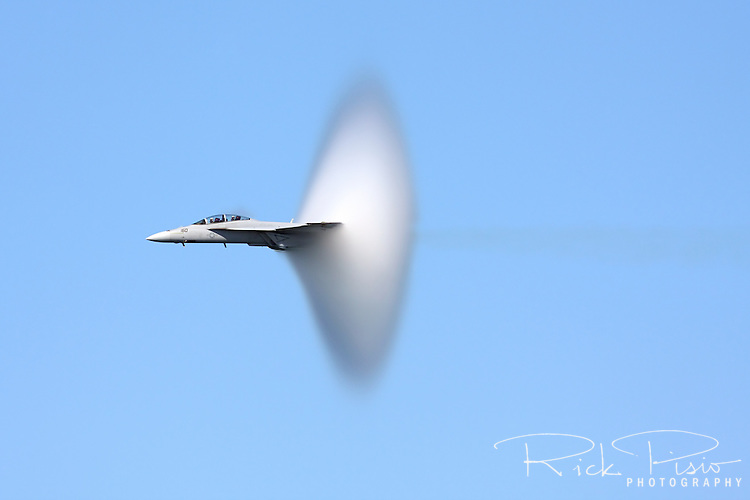 Vapor cone covers the tail of an F/A-18 Hornet during a high speed pass