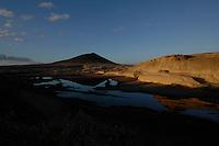 Reflections and red mountain on the shoreline, El Medano beach at dusk, El Medano, Tenerife, Canary Islands.