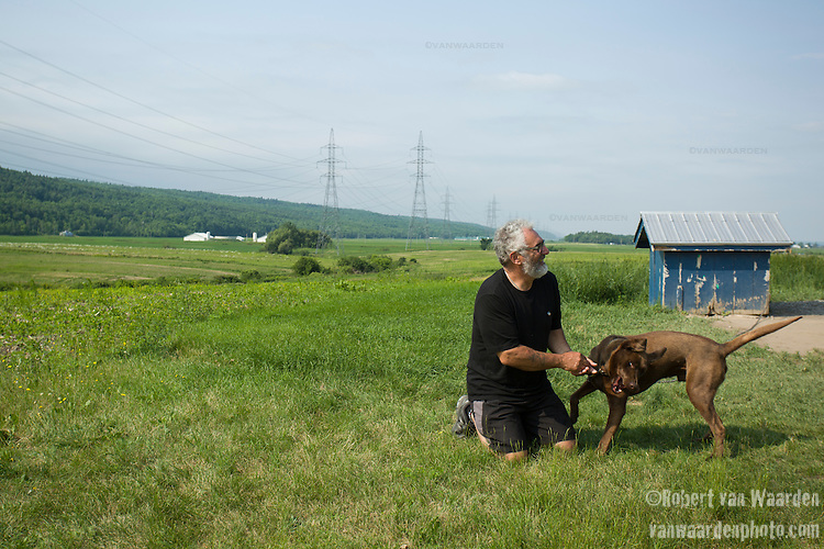 Clauder Bernier plays with his dog Moka on his property near Montmagny, Quebec. The proposed Energy East pipeline from TransCanada would run in the electrical tower corridor behind his house and he hates the idea. Many residents and communities in Quebec are concerned about the proposed Energy East pipeline and what it could mean for climate change, spills, disasters and investing in an industry that is of yesterday. (Credit: Robert van Waarden - http://alongthepipeline.com)