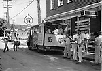 Cleanup operations along Bridge Street, Union City, came to a virtual standstill for a few minutes, as workers and residents gathered around this Salvation Army mobile canteen for fresh water, coffee or a sandwich. The unit, driven in from New York by Frank Webb in hard hat, was a welcome sight to the workers. Herbert Churchill, right, an employee at the Naugatuck Savings Banks, was in charge of the canteen.