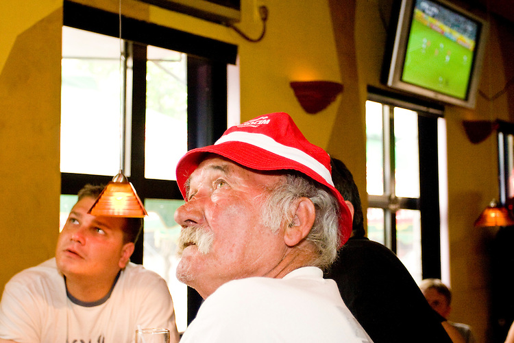 Poland fan Pan watches his team's World Cup match against Germany on June 14, 2006 at the Fireplace, a bar in a Polish section of Brooklyn.<br /> <br /> The World Cup, held every four years in different locales, is the world's pre-eminent sports tournament in the world's most popular sport, soccer (or football, as most of the world calls it).  Qualification for the World Cup is open to any country with a national team accredited by FIFA, world soccer's governing body. The first World Cup, organized by FIFA in response to the popularity of the first Olympic Games' soccer tournaments, was held in 1930 in Uruguay and was participated in by 13 nations.    <br /> <br /> As of 2010 there are 208 such teams.  The final field of the World Cup is narrowed down to 32 national teams in the three years preceding the tournament, with each region of the world allotted a specific number of spots.  <br /> <br /> The World Cup is the most widely regularly watched event in the world, with soccer teams being a source of national pride.  In most nations, the whole country is at a standstill when their team is playing in the tournament, everyone's eyes glued to their televisions or their ears to the radio, to see if their team will prevail.  While the United States in general is a conspicuous exception to the grip of World Cup fever there is one city that is a rather large exception to that rule.  In New York City, the most diverse city in a nation of immigrants, the melting pot that is America is on full display as fans of all nations gather in all possible venues to watch their teams and celebrate where they have come from.