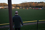 A half-time draw seller watching the first-half action at Lye Meadow as Alvechurch (in amber) hosted Highgate United in a Midland Football League premier division match. Originally founded in 1929 and reformed in 1996 after going bust, the club has plans to move from their current historic ground to a new purpose-built stadium in time for the 2017-18 season. Alvechurch won this particular match by 3-0, watched by 178 spectators, taking them back to the top of the league.