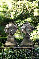 Two grey stone polyhedra occupy a rustic table in the garden