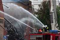 A day after the onset of the fire on a warehouse in the neighborhood of Barracas, firefighters continue working to control the fire. The deadly fire left eight firefighters and one emergency worker dead after the building collapsed on them.The warehouse, a 18th century nuilding, housed bank archives and was unnocupied at the time of the disaster. The government decreed two days of national mourning to honor the victims.